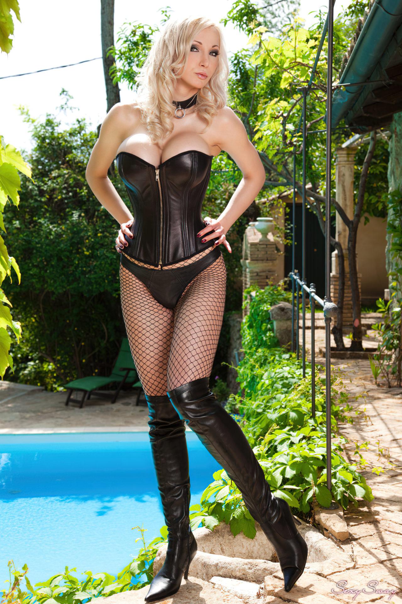 Mulher loira usando lingerie preta ao pé da piscina.